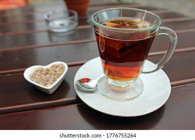 Close up of a glass cup of black tea including swimming tea bag on wooden table outside