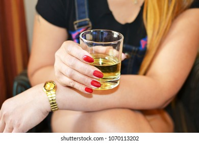 Close up of a glass of a drink in a female hand indoor relaxing on a couch