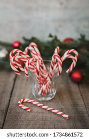 Close up of glass full of candy canes against Christmas backdrop.