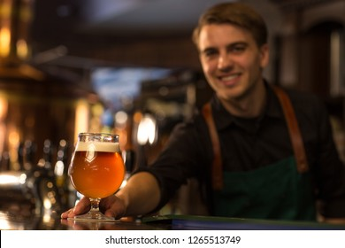 Close up of glass full of fresh delicious beer. Handsome bartender in dark green apron serving alcohol beverage on bar counter and smiling. Barman working in beer house or brewery.