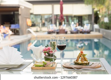 close up a glass of red wine and champagne with chicken satay on a table with poolside background