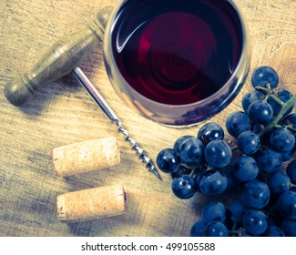 Close up - glass of red wine with a sprig of grapes on a wooden background.