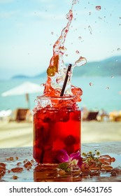 Close up of glass with refreshing strawberry cocktail with lime, mint with splashes on beach bar background