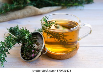 Close up of glass of rosemary herb tea, bunch of fresh rosemary and vintage tea infuser on wooden background.  Rustic style.