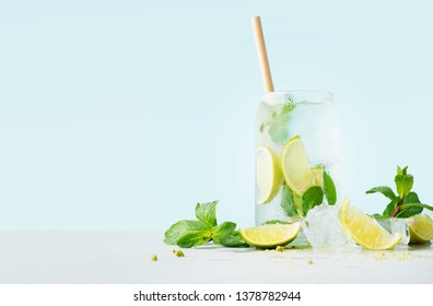 Close up of glass of tropical mojito cocktail on cyan pastel background with copy space. Summer time vacation concept.
