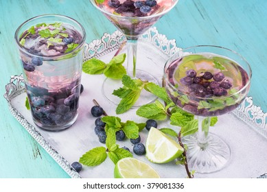 Close up of glasses of alcohol cocktail with blueberries and mint on a metal tray.