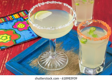 Close up of glasses with homemade margarita cocktail garnished with salt rim.