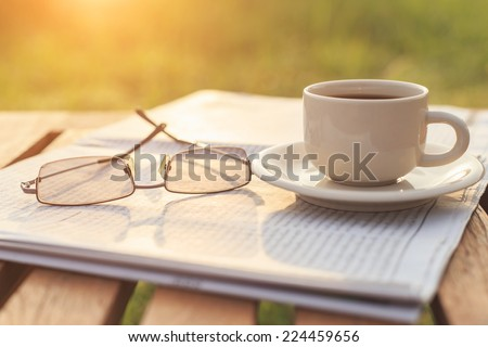 Close up glasses on newspaper and Coffee on the table in the morning