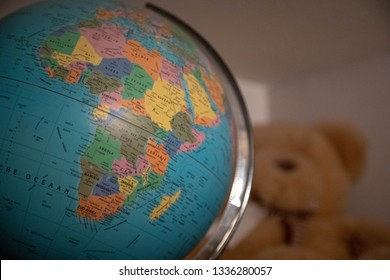 Close up of a globe with african continent, playful cuddly bear in the background. Nursery interior concept.