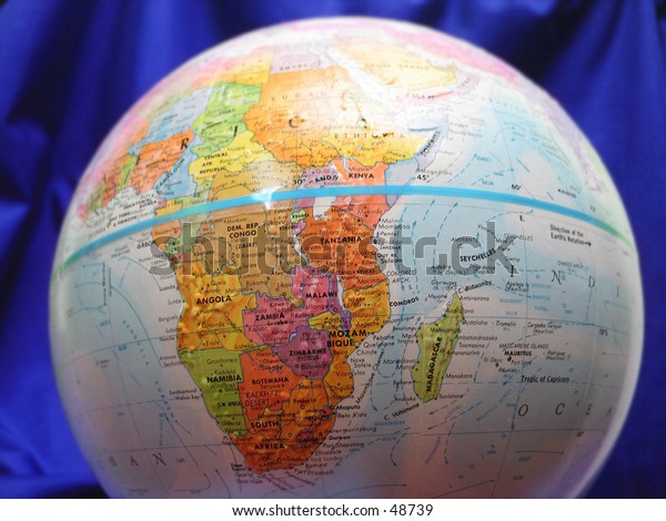 Close up of a globe, Blue material in background.