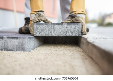Close Up Of The Gloved Hands Of A Builder Laying Outdoor Paving Slabs On A  Prepared