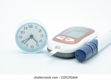 Close up of Glucose meter for check blood sugar level with Stethoscope, lancet and round clock on white background using as Time, Medicine, diabetes, glycemia, health care and people concept