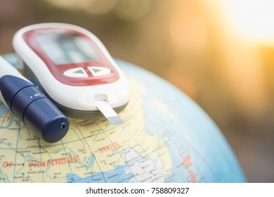 Close up of Glucose meter for check blood sugar level with lancet on world balloon using as World medicine, diabetes, glycemia, health care and people concept