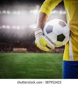 close up goalkeeper holding soccer ball in the stadium