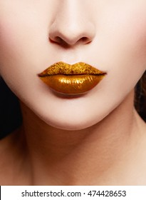 Close up of gold artistic lips. Glitter upper lip and shiny lower lip. Makeup cosmetic image.