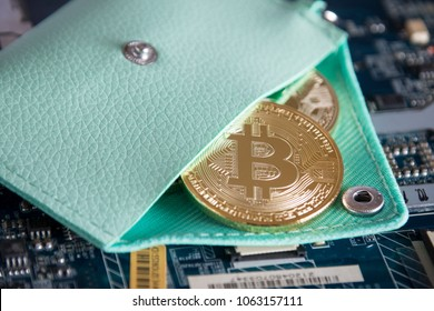 Close Up Gold Bitcoin Encrypted Digital Currency. Virtual Cryptocurrency In Coin Wallet On Computer Motherboard.