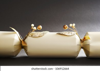 Close up of a gold Christmas cracker decorated with beads and pearls.