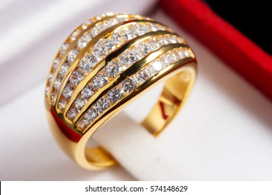 close up gold diamond ring in red ring box