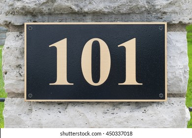 Close up gold house number one hundred one on Stone wall