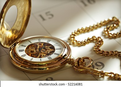 Close up of a gold pocket watch on a calendar in sunlight