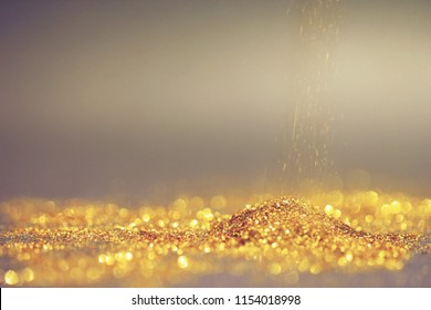 Close up of Gold powder with glitter lights on dark background