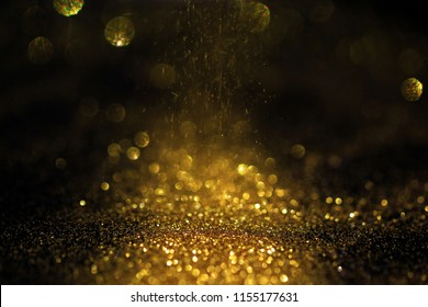 Close up of Gold powder with glitter lights on black background