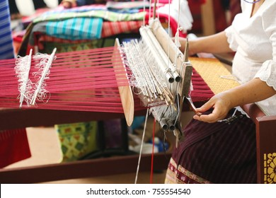 Close up of gold silk weaving on loom, cotton on the manual wood loom in Asian traditional culture and woman hand weave lifestyle