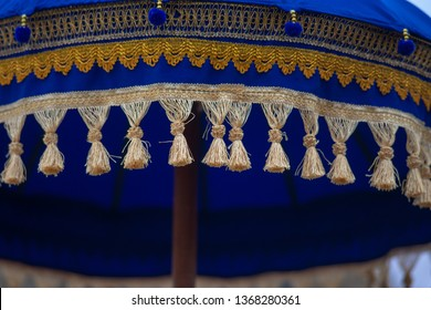 Close up of gold tassels and thread on blue Japanese umbrella