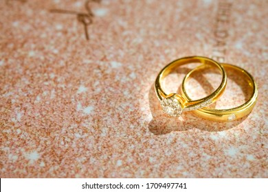 Close up of Gold wedding rings or engagement rings on wedding invitation card background. Couple ring beautiful and elegant. Gift for marry or celebrate. Love and Wedding concept with copy space.