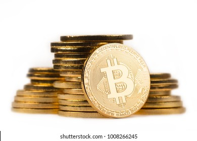 close up golden bitcoin in front of a pile of golden metallic coins isolated on white background