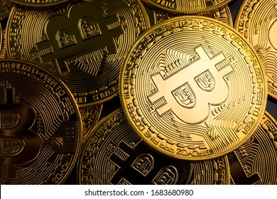 Close up of golden coins with bitcoin symbol background.