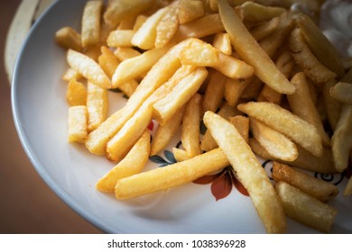 Close up of golden deep fried French fries. An American classic, fast food item, these potatoes are thin and crisp. Perfect chips ready to eat. Delicious comfort food or junk food. Taters on the side.