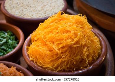 Close up of golden egg threads  dessert  in a wooden bowl