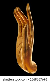 Close up of golden hand of Buddha statue over black background