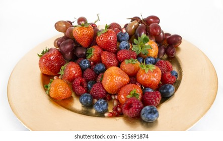 Close up of a golden plate with fruit. Strawberries, blueberries, raspberries, grapes, pomegranate seeds.