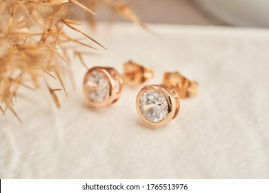 Close up golden stud earrings, with white crystals and diamonds. Beautiful earrings on white background. Women accessories