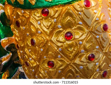 close up golden trousers decorative with red ruby of giant statues in the temple.