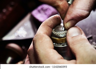 Close up of a goldsmith's hand making a gold or silver ring or a diamond using goldsmith's tools. For this work it takes precision and patience. Concept of: tradition, luxury, jewelry.