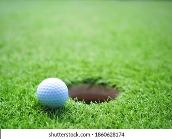 Close up golf ball beside hole (lip of cup) green grass with sunset light in evening. Selective focus.