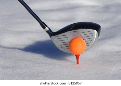 Close up of a golf ball and a club in snow
