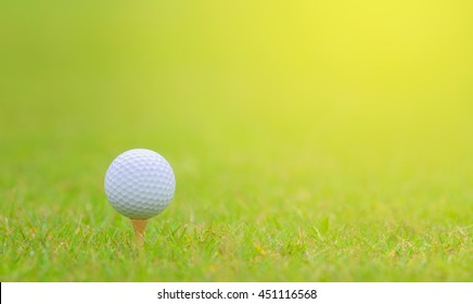 Close up of golf ball on tee at golf course with green meadow