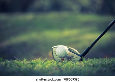 Close up of golf ball on a tee with golf club on the fairway.