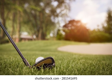 Close up of golf club with ball on tee, with fairway in background at sunset.