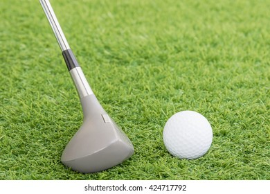 Close up golf club and ball on green grass