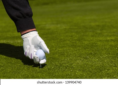 A close up of a golfer with a white glove placing a ball on a tee