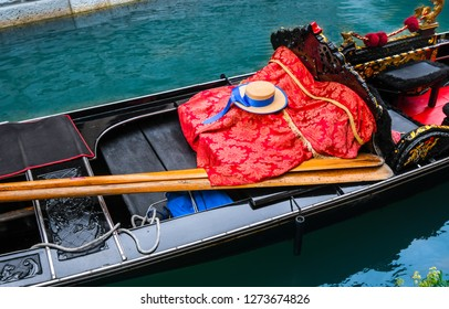A close up of a gondola with oars, gondolier hat and red blanket as it sits unoccupied in a canal in Venice, Italy