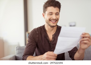 Close up Good Looking Young Bearded Guy Reading a Letter at the Couch with a Happy Facial Expression
