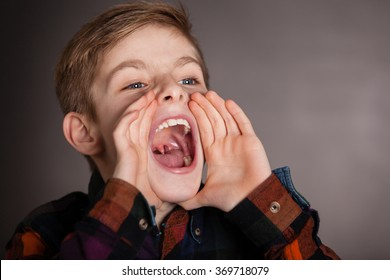 Close up Good Looking Young Boy Yelling Into the Distance with Mouth Wide Open Against Gray Background