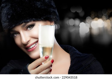 Close up of a gorgeous chic young woman in winter fur fashion celebrating the New Year with a flute of bubbly champagne toasting the viewer with a lovely wide smile, dark background with copy space