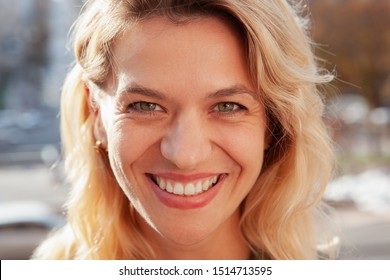 Close up of a gorgeous happy mature woman smiling to the camera. Cropped shot of  face of a cheerful attractive woman laughing